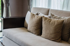 Brown pillows on modern sofa Stock Images