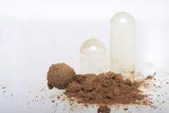 The brown pills are scattered over the white surface. One active ingredient is poured from one pill. View from above. The brown pills are scattered over the Stock Images