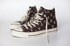 Brown pirate keds. Brown shoes with a pirate skull image Royalty Free Stock Photo