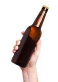 Brown piwna butelka w ręce odizolowywającej na białym tle Zdjęcie Stock