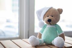 Brown-Plüschtierteddybär in der Minze-farbigen Kleidung und im weißen Hut auf dem Holz Lizenzfreies Stockbild