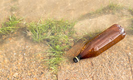 Brown Plastic Bottle in River Royalty Free Stock Photos