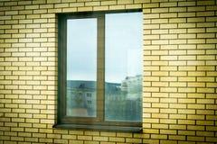 Brown-Plastikfenster in einem Backsteinhaus lizenzfreie stockfotos