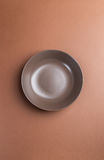 Brown plate on brown background,above view.Useful as a food back Stock Photos