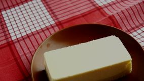 Brown plate with a piece of classic new York cheesecake, spinning on a red checkered napkin.  stock footage