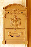 A brown postbox. On the wall with a greek democracy emblem Stock Images