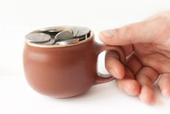 Brown Pot and Coins with human hand Stock Image