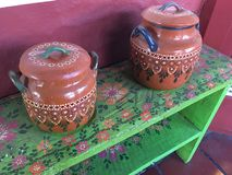 Brown Pots on Green Bench. Hand- painted brown pots are displayed on green bench royalty free stock photography