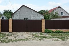 Brown fence and closed gates made of metal and bricks near the road. Brown private fence and closed gates made of metal and bricks near the road royalty free stock photo