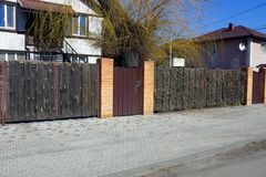 Brown long wooden fence and closed door on a gray asphalt road. Brown private long wooden fence and closed door on a gray asphalt road outside stock photography