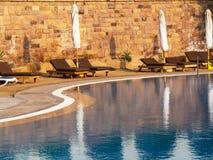 Brown puści sunbeds blisko basenu z zamkniętymi parasolami przy wschód słońca obraz royalty free