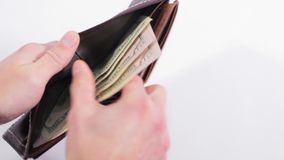 Brown purse on white background. Man recounts the cash from the purse and takes all. Close up