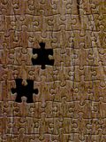 Brown puzzle texture with two missing pieces. Abstract colored background with brown puzzle texture and missing pieces Stock Photography