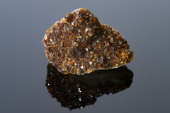 Brown quartz on black reflective surface Royalty Free Stock Image