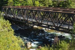 Brown railway bridge over river Adige, Trentino, Italy stock image