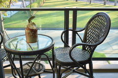Brown rattan chair on balcony overlooking a garden Stock Photography
