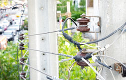Brown-red  electrical Insulator which is binded by high voltage. Power lines on electricity post at roadside Stock Photo