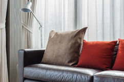 Brown and red pillow on modern sofa with lamp Royalty Free Stock Image