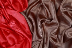 Brown and red silk satin cloth of wavy folds texture background Stock Photos