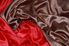 Brown and red silk satin cloth of wavy folds texture background Stock Photography
