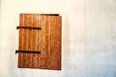 Brown red wooden window with rusted metal hinges on a white cement wall detail. The old window is hanging tilting and only partly closing the wall, both Royalty Free Stock Photos