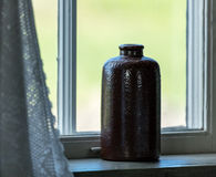 Brown retro ceramics bottle on window. With white curtain Stock Photos