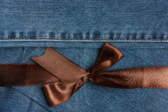 Brown ribbon on blue jeans texture Stock Images