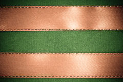 Brown ribbon on green fabric background with copy space. Royalty Free Stock Images