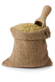 Brown rice. Brown natural long rice in small burlap sack Royalty Free Stock Images