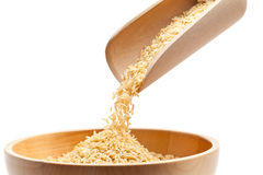 Brown rice. Raw organic brown rice filled into wooden bowl over white background Royalty Free Stock Photography