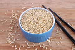 Brown rice in blue bowl Stock Photos