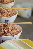 Brown rice with chopsticks in cup. Stock Image