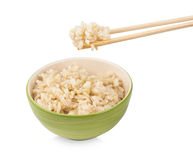 Brown rice with chopsticks in a cup on white background Royalty Free Stock Photos