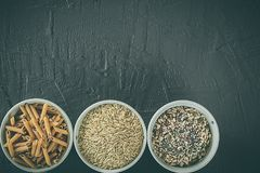 Brown rice grains, seeds and whole grain pasta in a bowl. Healthy food. Space for writing. Brown rice grains, seeds and whole grain pasta in a bowl. Healthy and stock photos