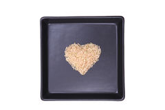 Brown rice. Rice heart shape as black plate Royalty Free Stock Photo