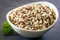 Brown Rice and Quinoa in White Bowl over Slate royalty free stock photography