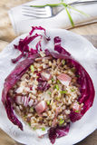 Brown rice with red radicchio and speck Stock Images