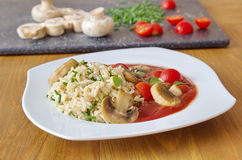 Brown rice with tomatoes, sauce and champignons Stock Image