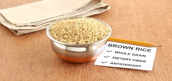 Healthy Food Brown Rice. Brown rice, which is a whole grain and healthy food, in a copper bowl, with a note of some of its benefits, on a wooden background Stock Photos