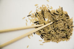 Brown rice on white with chopsticks Royalty Free Stock Image