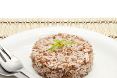Brown rice on a white plate. Cook brown rice on a white plate on a bamboo mat Stock Photos