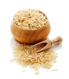 Brown rice in a wooden bowl with a shovel on a white background. Royalty Free Stock Photo