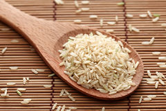 Brown rice in a wooden spoon. On bamboo napkin. Close-up Royalty Free Stock Images