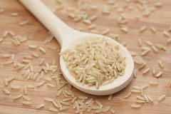 Brown rice in a wooden spoon Stock Images