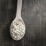 Brown rice in wooden spoon Stock Photo