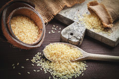Brown rice. Yellow, used for risotto in burlap sack jute on a wooden cutting board Royalty Free Stock Image