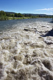Brown River Rapids and Blue Sky Stock Image