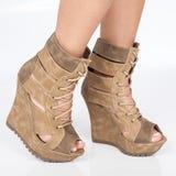Brown riveste di pelle le scarpe con la zeppa sullo stivale con mettere beige dei pizzi nei piedi della donna sul fondo bianco immagine stock