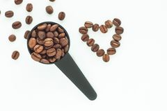 Brown roasted coffee beans in a black measuring spoon on a white background isolated. Brown roasted coffee beans in a black measuring spoon and a heart of beans royalty free stock photo
