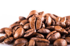 Brown roasted coffee beans close up on white background. Brown roasted coffee beans macro on white background Stock Images